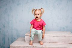 Free Little Funny Blue-eyed Girl Child Blonde With A Haircut Two Ponytails On Her Head Sitting On A Gossip On The Background Of An Old Stock Photo - 110025870