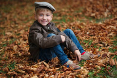 Little funny boy in autumn leaves portrait Royalty Free Stock Image