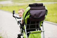 Little funny boy with baby carriage Stock Photos