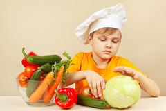 Little funny boy chooses vegetables for salad at table Stock Images