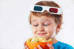 Little funny boy in 3D glasses with bowl of popcorn Stock Photos