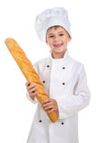 Little funny boy dressed in chef uniform with fresh baguette. Stock Photos