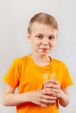 Little funny boy drinking fresh cola through a straw Stock Photography