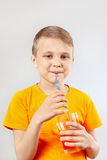 Little funny boy drinking fresh red lemonade through a straw Royalty Free Stock Image