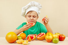 Little funny boy eat fresh grapefruit at table with fruits Royalty Free Stock Photos