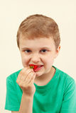 Little funny boy eating fresh red strawberry Stock Photography