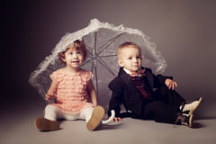 Little funny boy and girl under umbrella Royalty Free Stock Images