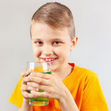 Little funny boy with glass of green lemonade Royalty Free Stock Images