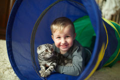 Little funny boy hugs cat Stock Images