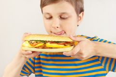 Little funny boy is licked at cheeseburger on white background royalty free stock photo