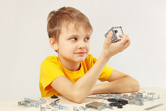 Little funny boy made something of mechanical constructor. Little funny boy made something of the mechanical constructor royalty free stock image