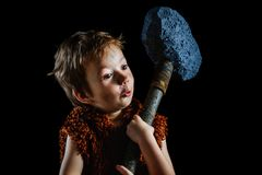 Little funny boy is a Neanderthal or a Cro-Magnon. An ancient caveman with a huge ax is isolated on a black. Background. Shaggy and dirty savage, warrior stock images