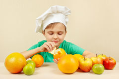 Little funny boy peeling fresh orange at table with fruits Royalty Free Stock Photo