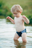 Little funny boy playing in water Royalty Free Stock Photo