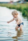 Little funny boy playing in water Stock Photography