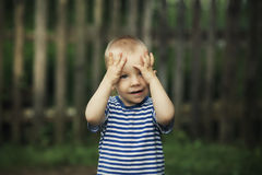 Little funny boy plays hide and seek Royalty Free Stock Photos