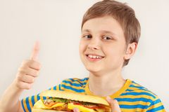 Little funny boy recommends and likes big cheeseburger on white background royalty free stock image