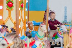 Little funny boy riding on the horse is a roundabout carousel in an amusement park. Happy child, having fun outdoors on a sunny da royalty free stock photos