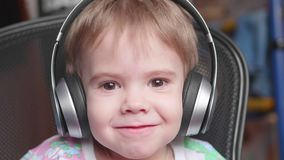 A little funny boy sits in a chair and listens to music through headphones. Face close up Stock Photo