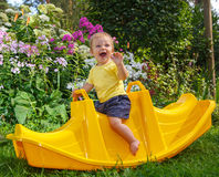 Little funny boy sitting on baby swing. Smiling and laughing Royalty Free Stock Images