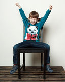 Little funny  boy is sitting on the chair, hands up, eyes are cl Royalty Free Stock Images