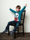 Little funny  boy is sitting on the chair, hands up, smiling Royalty Free Stock Photography