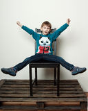 Little funny  boy is sitting on the chair, piddling, fooling Royalty Free Stock Photography