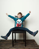 Little funny  boy is sitting on the chair, piddling, fooling Stock Photo
