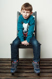 Little funny  boy is sitting on the chair, piddling, fooling Stock Image