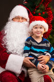 Little funny boy sitting on Santa Claus laps. Stock Images
