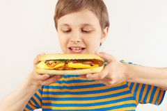 Little funny boy in a striped shirt with a cheeseburger on white background royalty free stock photography