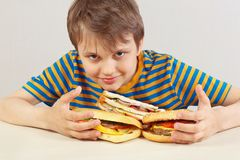 Little funny boy in a striped shirt at the table with hamburgers and sandwich on white background stock images