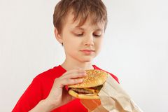 Little funny boy take out a hamburger from a package on white background stock images