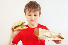 Little funny boy take out a hamburger from a paper package on white background stock photography