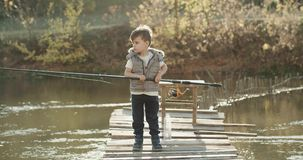Little funny boy teaching how to fish on the lake he holding a big fishing rod. stock footage