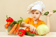 Little funny boy with vegetables at table Stock Image