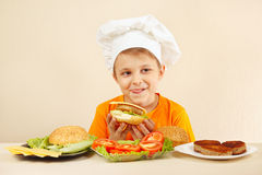 Little funny chef appetizing licked near cooked hamburger Royalty Free Stock Images