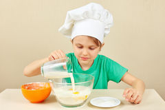 Little funny chef pours milk for baking cake Royalty Free Stock Image
