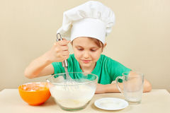 Little funny chef prepares the dough for baking cake Royalty Free Stock Photos