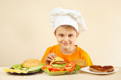 Little funny chef puts cheese on hamburger Royalty Free Stock Images