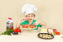 Little funny chef puts the ingredients on pizza crust Royalty Free Stock Photos