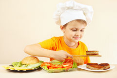 Little funny chef puts meat on hamburger Royalty Free Stock Photo