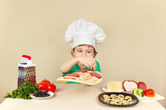 Little funny chef puts olives on pizza crust Stock Photo