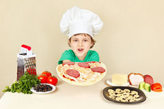 Little funny chef puts sausage on pizza crust Royalty Free Stock Images