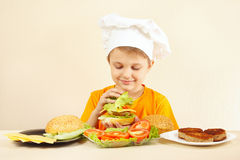 Little funny chef shows how to cook hamburger Royalty Free Stock Photography