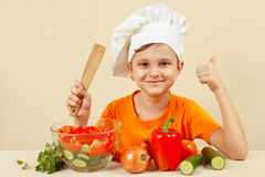 Little funny chef shows how to cook vegetable salad Royalty Free Stock Images