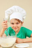 Little funny chef shuffles dough for baking cake Royalty Free Stock Photography