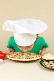 Little funny chef sniffing aroma of cooked pizza Stock Photos