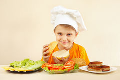 Little funny chef at the table with ingredients is going to cook hamburger Royalty Free Stock Images