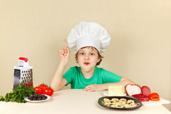 Little funny chef at table with ingredients for pizza Stock Photography